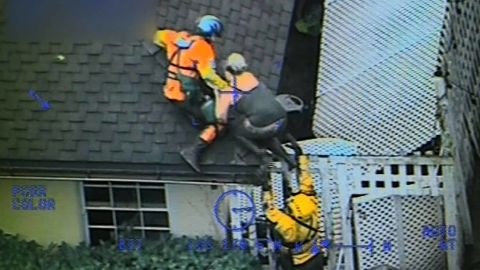 The Coast Guard crew pulls a person onto the roof after a river of mud flowed through the house.