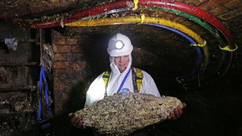A sewer technician holds a fatberg in a London sewer in 2014.