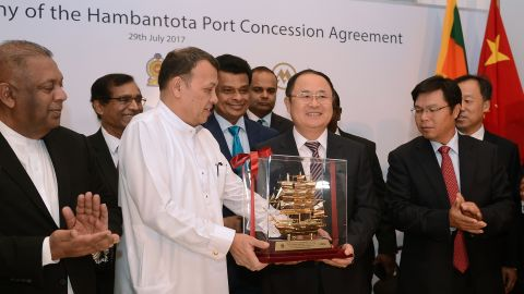 Sri Lanka's Minister of Ports & Shipping Mahinda Samarasinghe exchanges souvenirs during the Hambantota International Port Concession Agreement at a signing ceremony in Colombo in 2017.