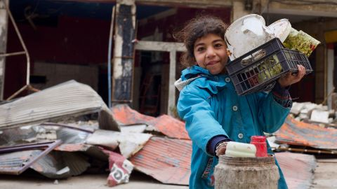 A young girl in the town of Maraat Nouman with her haul for the day. She's just finished picking through the garbage around the site of a recent airstrike for reusable plastic.