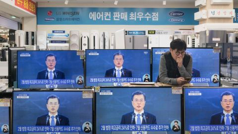 """A live broadcast shows South Korea's President Moon Jae-In delivering his New Year's address on television screens at an electronics mall in Seoul on January 10, 2018. Denuclearisation of the Korean peninsula is """"the path to peace and our goal"""", South Korean President Moon Jae-In said, a day after the North agreed to send its athletes to the Winter Olympics in his country. / AFP PHOTO / Ed JONES        (Photo credit should read ED JONES/AFP/Getty Images)"""