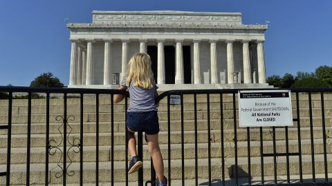 A child stands on the barricade around the Lincoln Memorial in Washington, DC, on October 2, 2013, on the second day of the federal government shutdown. US President Barack Obama on Wednesday called congressional leaders to a White House meeting, providing a glimmer of hope for movement on day two of a crippling government shutdown. The White House is squaring off with Republican rivals in Congress over how to fund federal agencies, many of which are now closed, leaving some 800,000 furloughed workers in the lurch and a fragile economy at risk. AFP Photo/Jewel Samad        (Photo credit should read JEWEL SAMAD/AFP/Getty Images)