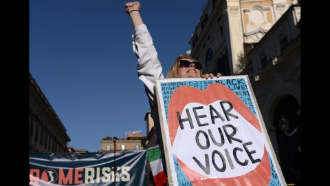 A woman lifts her fist while holding a banner during a Women's March demonstration in Rome on Saturday.