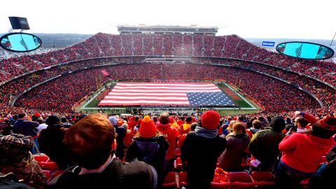 Fans stand at attention for the national anthem overlooking a 100 yard American flag prior the AFC Wild Card Playoff Game between the Kansas City Chiefs and the Tennessee Titans at Arrowhead Stadium on January 6, 2018 in Kansas City, Missouri.