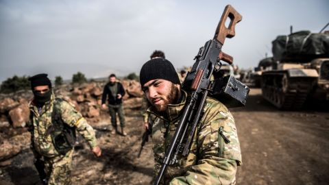 """TOPSHOT - Turkish troops advance near the Syria border at Hassa, Hatay province, on January 22, 2018, as part of the operation """"Olive Branch"""", launched two days ago. The operation aims to oust the People's Protection Units (YPG) militia, which Turkey considers to be a terror group, from its enclave of Afrin. / AFP PHOTO / BULENT KILIC        (Photo credit should read BULENT KILIC/AFP/Getty Images)"""