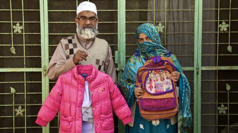 Muhammad Amin Ansari and Nusrat Amin -- the parents of Zainab Ansari -- hold up her school uniform, jacket and schoolbag.