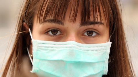 LONDON, ENGLAND - JULY 30:  A woman wearing a surgical mask to prevent the transmission of airborne infection walks in Westminster on July 30, 2009 in London, England. Figures released by the Health Protection Agency show that by July 19, an estimated 100,000 Britons have been infected with swine flu and there have been 26 deaths in England linked to the disease. Over 700 people worldwide have died after contracting swine flu which is spreading faster than any other flu pandemic.  (Photo by Oli Scarff/Getty Images)