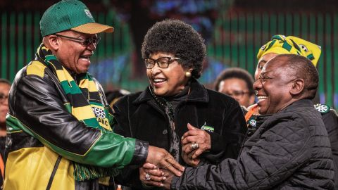 """Madikizela-Mandela joins the hands of South African President <a href=""""http://www.cnn.com/2018/02/08/africa/gallery/jacob-zuma-career/index.html"""" target=""""_blank"""">Jacob Zuma, </a>left, and Deputy President Cyril Ramaphosa during an African National Congress policy conference in 2017."""