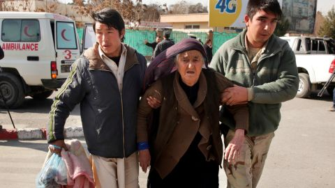 A wounded woman is assisted at the site of the attack Saturday in Kabul.