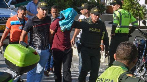 Police escort a suspect arrested in Saturday's blast in Barranquilla.