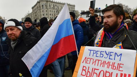 """One protester in Moscow brandishes a placard saying: """"Demand lawful election."""""""