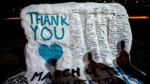 """Shadows of Michigan State University students fall on """"The Rock"""" as they examine its new, hand-painted tribute to Larry Nassar's victims."""