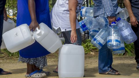 People queue to collect water from a natural spring outlet in the South African Breweries in Cape Town.