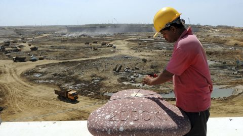 Sri Lankan construction workers operate heavy equipment at the base of the Hambantota port August 1, 2010.
