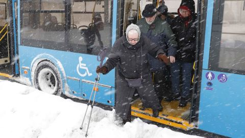 A passenger gingerly leaves a bus during the blizzard in Moscow.