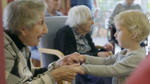 Fay Garcia, 90, visits with a child from her care home's on-site nursery.