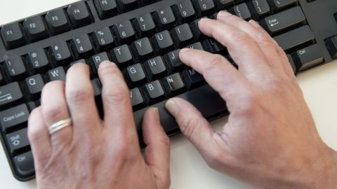 """A man types on a computer keyboard in this photo illustration taken in Washington, DC, November 21, 2016. Almost half of US internet users say they have been a victim of online harassment or abuse ranging from name-calling to stalking to physical threats, a survey showed November 21, 2016. Women, the under-30s, and people identifying as lesbian, gay, or bisexual were all more likely to experience such harassment -- and were also more likely to self-censor what they post online as a result, researchers found.More than a third (36 percent) had suffered """"direct harassment,"""" including being called offensive names, threatened physically or stalked.  / AFP PHOTO / SAUL LOEB        (Photo credit should read SAUL LOEB/AFP/Getty Images)"""