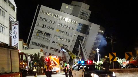 Rescuers are seen entering a building that collapsed onto its side from an early morning 6.4 magnitude earthquake in Hualien County, eastern Taiwan, Wednesday, February. 7.  Rescue workers are searching for any survivors trapped inside the building.