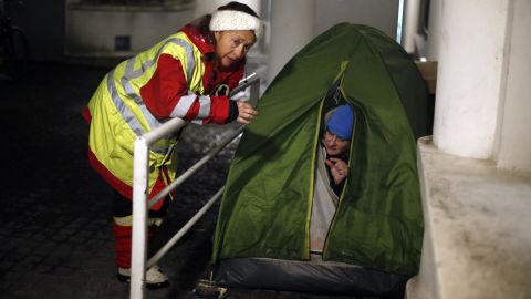 A volunteer worker talks with a homeless woman in Issy les Moulineaux, west of Paris, on Tuesday.