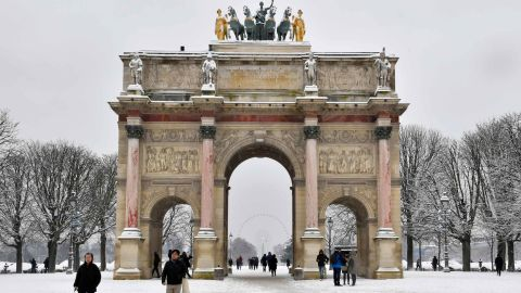 People pass by the Arc de Triomphe du Carrousel as they walk through the snow covered Tuileries garden.