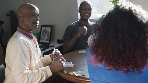 Ira Weddington, a Marine Corps veteran, plays cards with family and friends in his new tiny house.