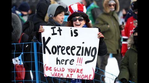 A spectator holds a sign at the men's snowboarding slopestyle final.