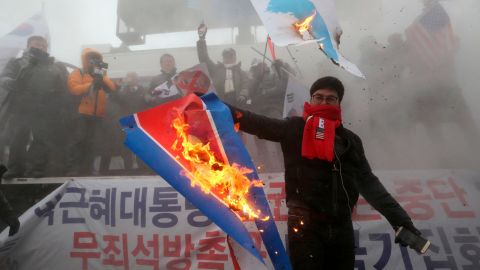 A protester burns a North Korean flag during a rally against North Korea's participation in the 2018 Pyeongchang Winter Olympics.
