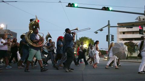 NEW ORLEANS, LA - AUGUST 29: People walk through the streets with a band during a second line parade marking the 10th anniversary of Hurricane Katrina  on August 29, 2015 in New Orleans, Louisiana. Hurricane Katrina killed at least 1836 people and is considered the costliest natural disaster in U.S. history.  (Photo by Joe Raedle/Getty Images)