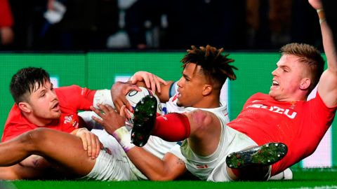 """After Anthony Watson (C) and Gareth Anscombe (R) dived at a kick in England's in-goal area, the television match official ruled that Watson had touched the ball down first. Wales coach Warren Gatland felt his side was denied a try, calling the decision a """"terrible mistake"""" in what turned out to be a tightly-contested affair."""