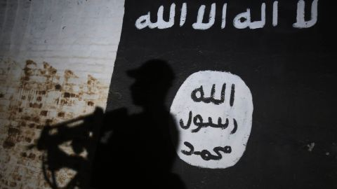 TOPSHOT - A member of the Iraqi forces walks past a mural bearing the logo of the Islamic State (IS) group in a tunnel that was reportedly used as a training centre by the jihadists, on March 1, 2017, in the village of Albu Sayf, on the southern outskirts of Mosul.Iraqi forces launched a major push on February 19 to recapture the west of Mosul from the Islamic State jihadist group, retaking the airport and then advancing north. / AFP PHOTO / AHMAD AL-RUBAYE        (Photo credit should read AHMAD AL-RUBAYE/AFP/Getty Images)
