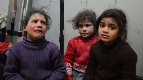Children cry at a makeshift hospital in Douma.