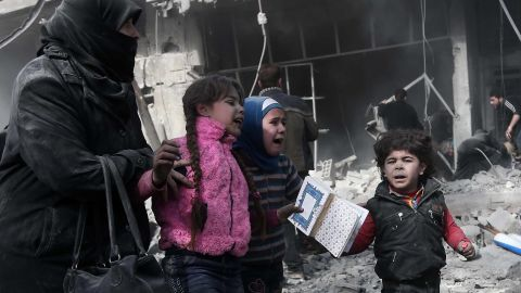 A woman and children run for cover after bombing in Hamouria on Monday, February 19.