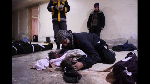 A man weeps over his child, who was killed in the Mesraba airstrikes.