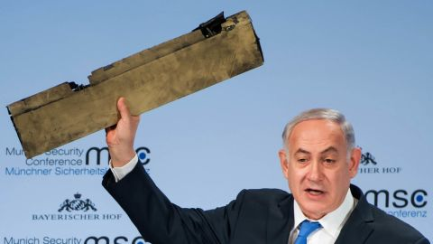Netanyahu, speaking at a security conference in Germany in February 2018, holds up what he claimed is a piece of an Iranian drone that was shot down after it flew over Israeli territory.