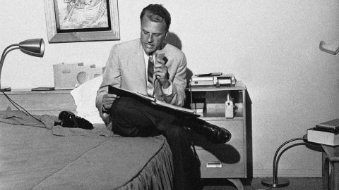 Graham dictates a synopsis of his evening sermon into a tape recorder in 1962. Secretaries would then type the synopsis for distribution to the press. Graham was conducting an eight-day crusade in Fresno, California.
