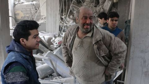 Syrians look for survivors at the site of strikes in Douma, in  Eastern Ghouta, on Thursday.
