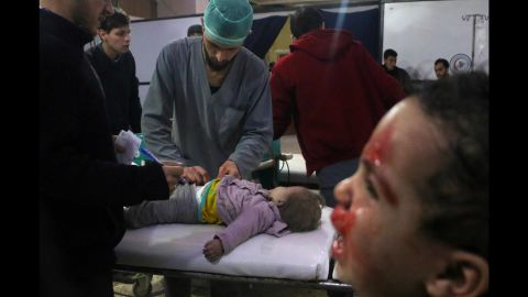 """Medics tend to a baby as a child cries next to them at a makeshift clinic in Douma, Syria, on Thursday, February 23. <a href=""""https://www.cnn.com/2018/02/23/middleeast/syria-eastern-ghouta-bombardment-fire-rockets-intl/index.html"""" target=""""_blank"""">More than 400 civilians have been killed</a> this week in Syria's rebel-held Eastern Ghouta region, according to the head of the region's health department on Friday, February 23. Syrian regime forces have been pounding Eastern Ghouta with shells, mortars and bombs."""