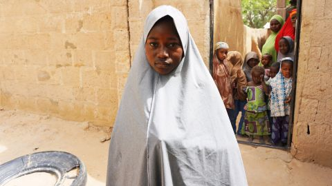 """TOPSHOT - Hassana Mohammed, 13, who scaled a fence to escape an alleged Boko Haram attack on her Government Girls Science and Technical College, stands outside her home in Dapchi, Nigeria, on February 22, 2018. Anger erupted in a town in remote northeast Nigeria on February 22 after officials fumbled to account for scores of schoolgirls from the college who locals say have been kidnapped by Boko Haram jihadists. Police said on February 21 that 111 girls from the college were unaccounted for following a jihadist raid late on February 19. Hours later, Abdullahi Bego, spokesman for Yobe state governor Ibrahim Gaidam, said """"some of the girls"""" had been rescued by troops """"from the terrorists who abducted them"""". But on a visit to Dapchi on Thursday, Gaidam appeared to question whether there had been any abduction. / AFP PHOTO / AMINU ABUBAKAR        (Photo credit should read AMINU ABUBAKAR/AFP/Getty Images)"""