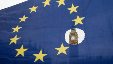 A pro-remain protester holds up an EU flag with one of the stars symbolically cut out in front of the Houses of Parliament on March 29, 2017.