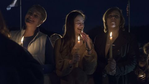 Susie Garrison, left, a teacher at Capital High School, student Amelia Engle from George Washington High School and Nitro High School teacher Kizmet Chandler take part in a candlelight rally in support of the statewide teacher walkout outside of the capitol building in Charleston, West Virginia, on Sunday.