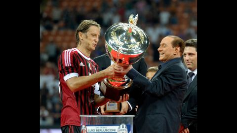 Berlusconi hands the Berlusconi Trophy to AC Milan's Massimo Ambrosini in August 2011. The trophy is awarded annually to the winner of a friendly football match in Milan.