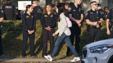 Marjory Stoneman Douglas High School staff, teachers and students return to school greeted by police and well wishers in Parkland, Florida on February 28, 2018. Students grieving for slain classmates prepared for an emotional return Wednesday to their Florida high school, where a mass shooting shocked the nation and led teen survivors to spur a growing movement to tighten America's gun laws. The community of Parkland, Florida, where residents were plunged into tragedy two weeks ago, steeled itself for the resumption of classes at Marjory Stoneman Douglas High School, where nearby flower-draped memorials and 17 white crosses pay tribute to the 14 students and three staff members who were murdered by a former student. / AFP PHOTO / RHONA WISE        (Photo credit should read RHONA WISE/AFP/Getty Images)