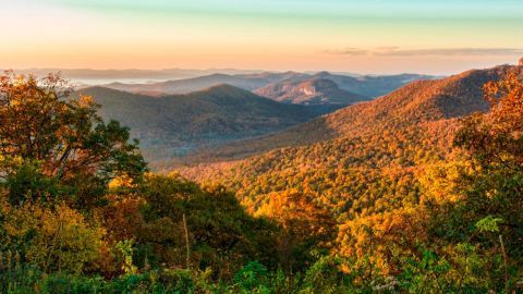 <strong>MOST POPULAR NATIONAL PARK SERVICE SITES: 1. Blue Ridge Parkway, North Carolina/Virginia:</strong> Blue Ridge Parkway meanders for 469 miles through two states, revealing gorgeous views of the Appalachian Highlands that vary by season. Autumn's changing foliage is evident in a sunrise view of the mountains in Brevard, North Carolina mountains near Asheville.