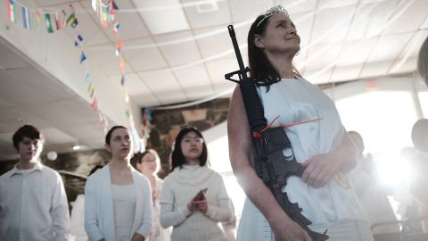 """NEWFOUNDLAND, PA - FEBRUARY 28:  A woman holds an AR-15 rifle during a ceremony at the World Peace and Unification Sanctuary in Newfoundland, Pennsylvania on February 28, 2018 in Newfoundland, Pennsylvania. The controversial church, which is led by the son of the late Rev. Sun Myung Moon, believes the AR-15 symbolizes the """"rod of iron"""" in the biblical book of Revelation, and it has encouraged couples to bring the weapons to a """"commitment ceremony"""" or """"Perfection Stage Book of Life Registration Blessing"""". Officials in the rural area in the Pocono Mountains have reportedly told elementary school parents that their children will be relocated on Wednesday to accommodate the AR-15 ceremony. The semiautomatic rifles are similar to the weapons used in a Florida high school shooting two weeks earlier.  (Photo by Spencer Platt/Getty Images)"""