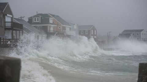 """Waves crash against homes in Scituate, Massachusetts, on Friday, March 2. A powerful nor'easter morphed into a """"bomb cyclone,"""" bringing rain, snow and heavy winds to parts of the East Coast."""
