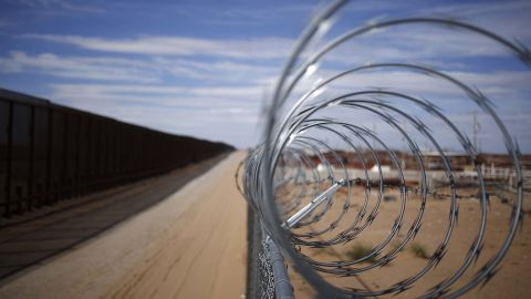 A concertina barbed wire fence stands next to a border fence that separates the U.S. and Mexico in New Mexico, U.S. Photographer: Luke Sharrett/Bloomberg