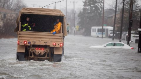 A National Guard vehicle takes emergency workers to rescue flood-trapped residents Friday in Quincy, Massachusetts.