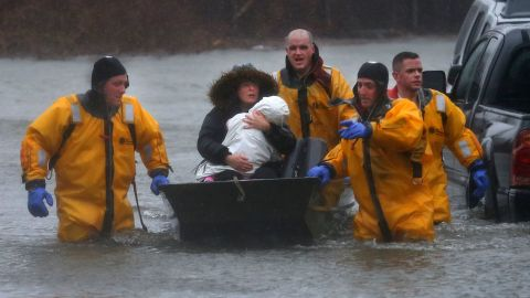 Rescuers help a mother and child leave their Quincy, Massachusetts, home by boat on March 2.