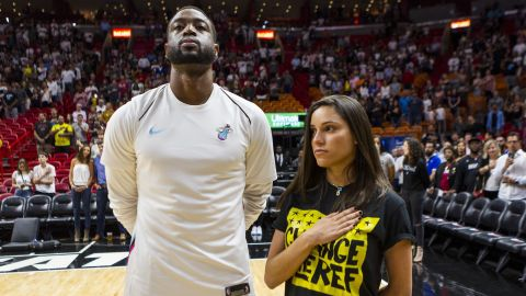Miami Dade's Dwyane Wade stands next Joaquin Oliver's sister, Andrea Ghersi, during the singing of the national anthem on Saturday.
