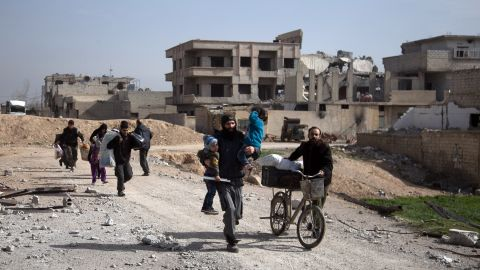 Syrians flee their homes with their belongings in the town of Beit Sawa in Syria's besieged eastern Ghouta region on March 4, 2018, following reported air strikes. Syria's regime seized control of over a quarter of rebel-held Eastern Ghouta on the edge of Damascus after two weeks of devastating bombardment, sending hundreds of civilians into flight, the Syrian Observatory for Human Rights said.